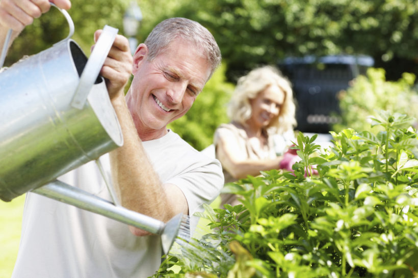 Portrait of a smiling senior man watering plants in the garden and blur woman in background